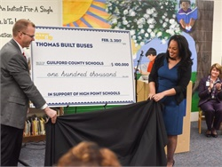 Thomas Built CEO Caley Edgerly presents a $100,000 pledge to Guilford County Schools Superintendent Sharon Contreras.