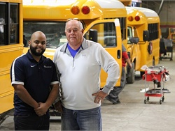 Trans Tech's all-electric eSeries school bus earned a spot on New York's Type A school bus contract. Shown here are Trans Tech President John Phraner (right) and National Sales Manager Erickson Lopez at Trans Tech's manufacturing facility.