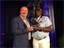 Transfinder President and CEO Antonio Civitella presents the company's Ambassador of the Year award to Kecia Ling, the director of transportation operations at Savannah-Chatham County (Ga.) Public School System.