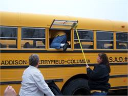 Maine School Administrative District #37 bus driver Clara Anne Freeman practices evacuating a bus via the side window emergency exit as part of a new training initiative. At left is driver Patricia Thaxter, and driver Darlene Stubbs is holding the window open.