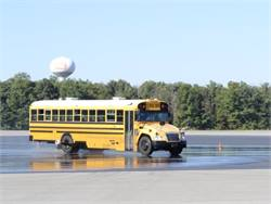 In a demonstration event, stability control technology helped keep a school bus from sliding out of its intended path while turning on a slippery surface — an epoxy-coated area that was sprayed with water.