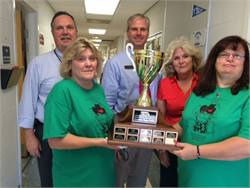 Sandy James (left) and Lori Partee of Henry County Schools hold the trophy for their win in the Georgia Special Needs Bus Roadeo. Behind them are Murry Chambers (left), assistant director of transportation, Cliff Shearouse, director of transportation, and Rosalyn Gibby, route supervisor and trainer for special-needs buses.