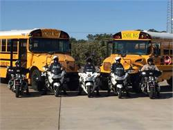 Police departments in the area of Leander, Texas, are conducting a regional initiative to promote school bus safety this week. Officers are pictured here with Leander Independent School District buses.