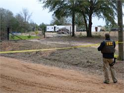 On the anniversary of the slaying of Alabama bus driver Charles Poland Jr., the New York Association for Pupil Transportation paid tribute to Poland and cited steps it is taking to increase school bus security. Pictured is an FBI agent near the bunker where a boy from Poland's bus was held hostage. Photo from FBI