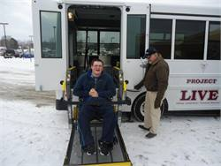 Michael, one of the Project LIVE students who helped raise money to buy a bus, boards their vehicle for the first time. Operating the wheelchair lift is Transportation Supervisor Roger Saxton.