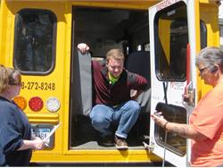 Moving from the driver's seat to the rear exit is one job-related task that may be timed in an agility test. Drivers and a bus monitor are shown here performing a New York physical performance test.