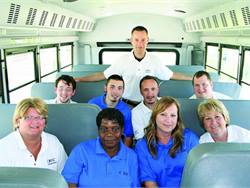 Justin Wilczynski became fascinated by school buses when he first rode one at age 4. He is pictured here (standing) with staff from his transportation department.