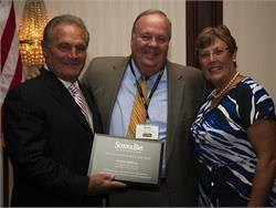 SBF Publisher Frank Di Giacomo (left) presents the Contractor of  the Year award to Kevin Clifford of Huntington Coach Corp. At right is  new NSTA President Magda Dimmendaal.
