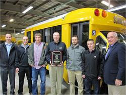 Leonard Bus Sales staff members receive the 2014 Dealer of the Year Award from Trans Tech President John Phraner (shown right.) Leonard Bus Sales President Mike Leonard is shown center, holding plaque.