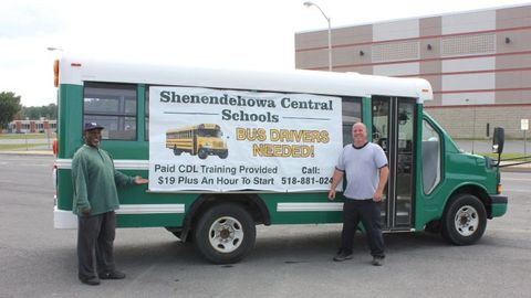 "Drivers Hershell Allen Jr. (left) and Donald Barnes Jr. show off Shenendehowa's ""advertisement bus."""