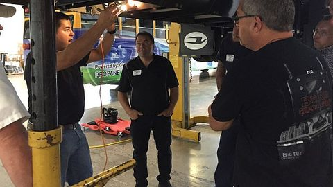 Maintenance personnel learn about servicing Blue Bird propane buses in a training session...