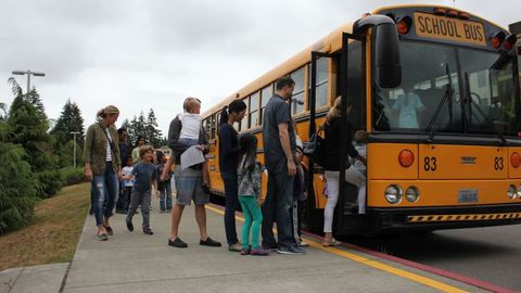 Families prepare to board buses for Issaquah (Wash.) School District's annual ride-along for...
