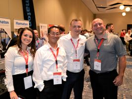 Sheila Stevens, Jim Chen and Eri Muca take care of Gregory Serafin at the Ateq booth.
