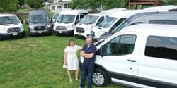 Rich Guernsey and Alexis Mahlum, owners of Rabbit Rentals, pose with their fleet of vans....