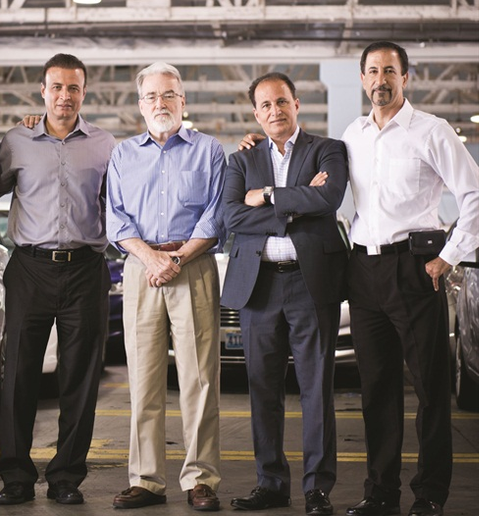Fox founders Mike Jaberi (grey shirt), co-owner Allen Rezapour (jacket), and Mark Mirtorabi (white shirt) assemble with Joe Knight, vice president of business development, inside the Fox Rent A Car location serving Los Angeles Airport.  - Photo by Vincent Taroc.