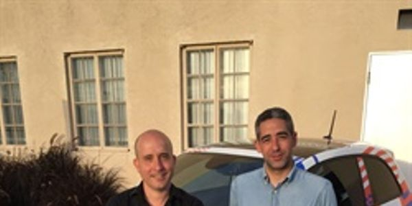 Co-founders Ori Sagie (left) and Aric Ohana stand in front of Envoy's branded community manager...