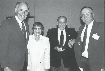 "In this photo from an early 90's Avis Licensee Association meeting, Vittoria (left) congratulates longtime Avis licensee Jay Weinberg (holding trophy) for winning the ""We Try Harder Award."" Weinberg is flanked by his wife and Avis Licensee Association Director Bob Kline. - Photo courtesy of Avis Licensee Association."