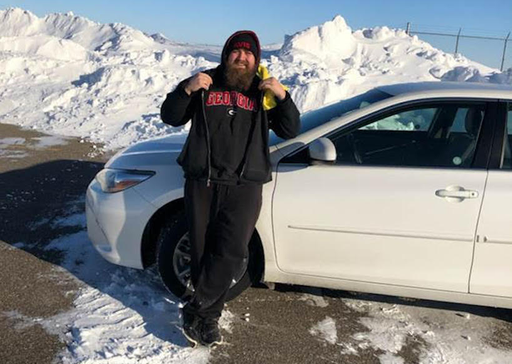 Dustin Laniel, a service agent at Avis Budget Fargo and diehard Georgia Bulldogs football fan, stands on the rental lot at Hector Int'l Airport in Fargo. Laniel regularly braves below-freezing temperatures to service vehicles - often in only a sweatshirt and beanie.  -