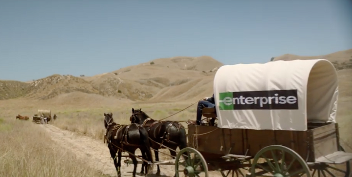 The 1800s family gets a taste of the future when the Enterprise associate has them sign for the rental with a mobile tablet to get them on their way. - Screenshot via Enterprise/YouTube.