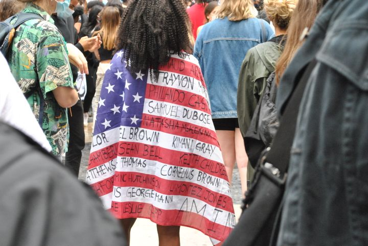 A protestor wears an American flag with the names of Black people who have been killed in the U.S. - Photo by Michaela Kwoka-Coleman.