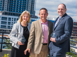 Angela Margolit (left) received the 2017 Professional of the Year Award in the vendor category and Phil Spink (right) won for the operator category. Chris Brown, executive editor of Auto Rental News (center) presented the awards.