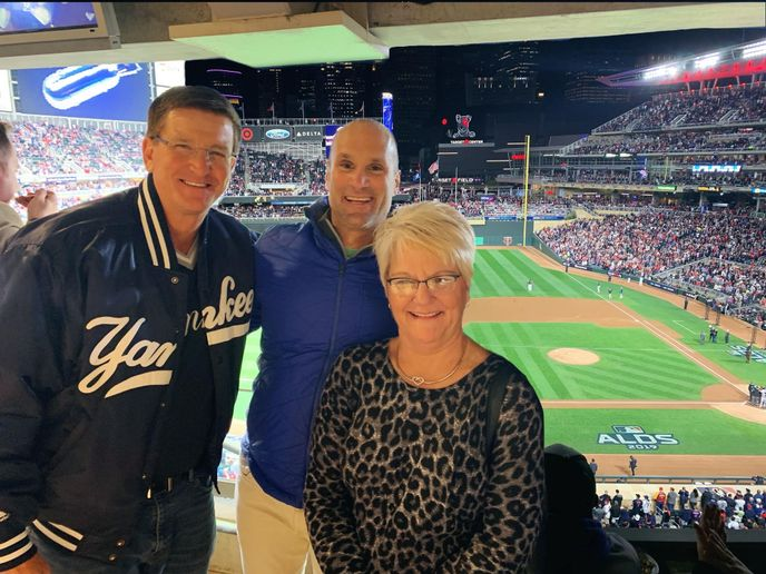Mike Muehlenfeld (left) takes in the Yankees/Twins playoff game last year with Claudia Kraemer (right) and Andrew Walser, owner of Walser Automotive Group. - Photo courtesy of Michael Muehlenfeld.