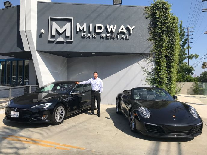 Midway Managing Director of sales and marketing Ryan Kerzner stands with two of the companies luxury rentals.  - Photo by Michaela Kwoka-Coleman.