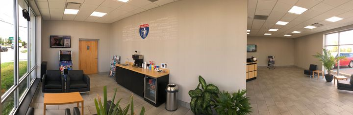 The service desk/reception area proudly displays all technicians' ASE certifications. -