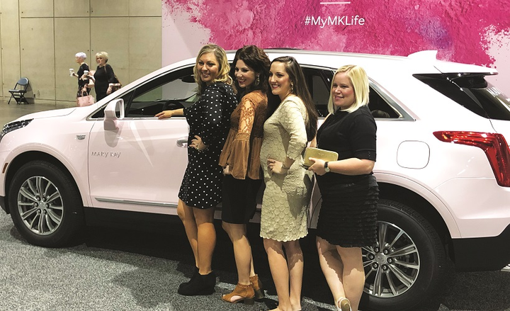 Mary Kay independent sales force members pose for a photo beside a pink Cadillac XT5. These photos are used as aspirational tools to help them achieve their sales goals so they too can earn a pink Cadillac.