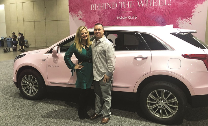 Mary Kay Independent Sales Director Cindy Sheppa poses with her husband beside a pink Cadillac XT5 on display at the Mary Kay Leadership Conference.