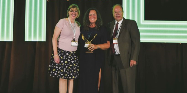 Erin Gilchrist (center), director of fleet for Safelite AutoGlass, received the 2019 Edward J....