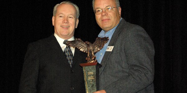 Bob Graham, ARI's vice president of Remarketing (left), receives the Consignor of the Year Award...