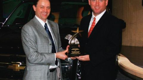 Brent Dewar, VP, Chevrolet Global Brand (left), accepts the Fleet Truck of the Year trophy for...