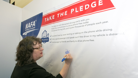 Photo of NAFA president, Ruth Alfson, signing the NAFA pledge to end distracted driving at the...