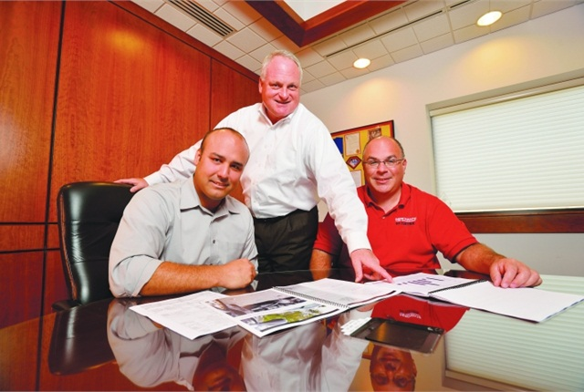 Tom Coffey, Merchants' VP of Sales and Marketing (center), Brad Jacobs, Merchants' manager of process improvement (left), and Dan Hannan, Merchants' director of strategic consulting, review a marketing plan.