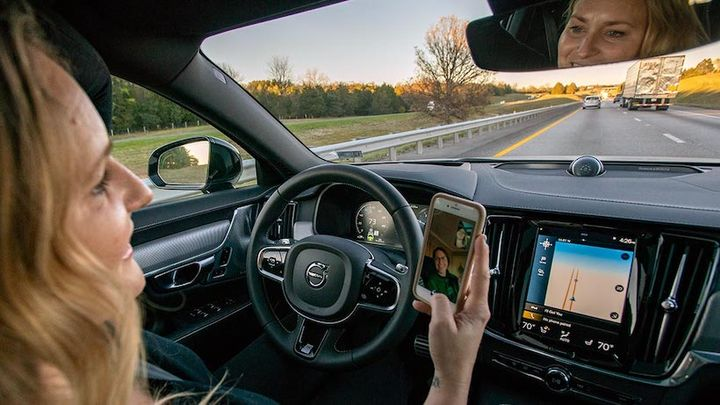 Drivers fidget with electronics and take both hands off the wheel more often as they develop trust in automated driver-assistance systems (ADAS). - Photo: IIHS