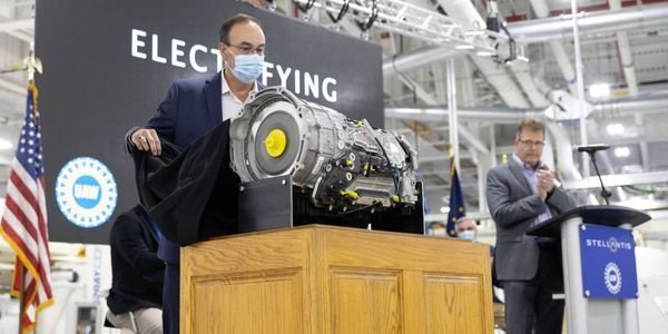 Stellantis' Dave Dukes (left) pulls the cover off the new, electrified eight-speed transmission...