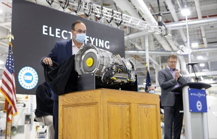Stellantis' Dave Dukes (left) pulls the cover off the new, electrified eight-speed transmission at the Kokomo Transmission Plant on Oct. 7. The new transmission will have the flexibility to be paired with internal combustion engines, as well as mild hybrid and plug-in hybrid propulsion systems. - Photo courtesy of Stellantis