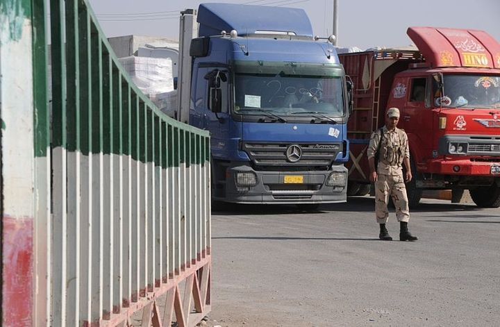 An Iranian border guard supervises the passage of trucks, full of manufactured goods and produce bound for the Shalamsha Port of Entry near Basra, Iraq, - Photo by Alan S. Brown, U.S. Army/Wikimedia Commons.