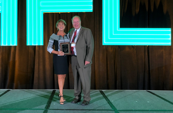 Theresa Ragozine (left) received a plaque representing her induction into the 2019 Fleet Hall of Fame from Automotive Fleet's Mike Antich (right). 