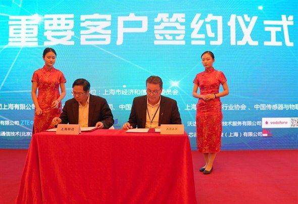 ABAX and China Mobile officials ink a 5-year partnership deal. Photo: ABAX