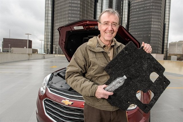 GM's Global Manager of Waste Reduction John Bradburn shows the Equinox engine insulation made from used water bottles. Photo courtesy of the automaker.