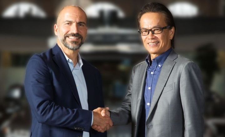 Dara Khosrowshahi, Uber's CEO (left) and Shigeki Tomoyama, executive vice president of Toyota Motor Corp. and president of Toyota Connected Company, shake hands on an agreement to collaborate toward bringing autonomous ride-hailing to market.