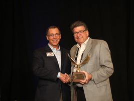 Dan Kennedy (left), retiring General Motors remarketing manager, accepts the Industry Leadership...