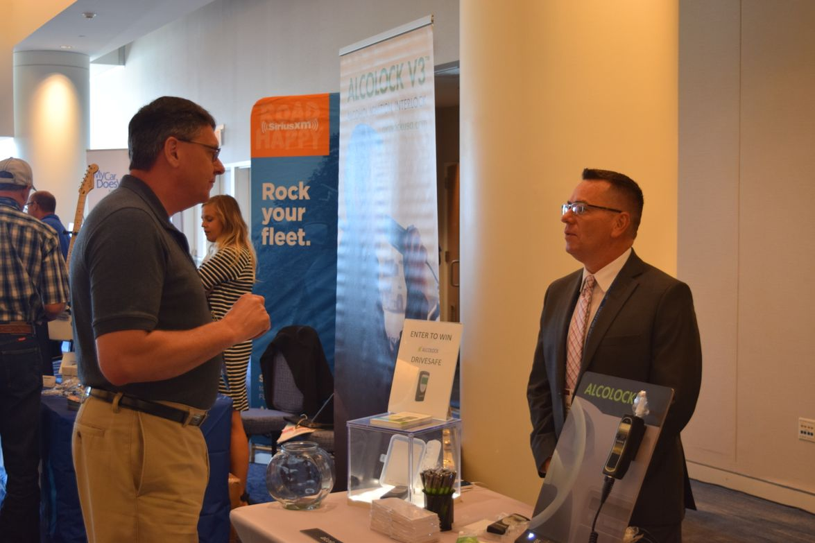 Phil Moser, vice president of Advance Driver Training Services, speaks with Bill Sheperd,...