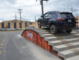 A driver and fleet customer riding in the Jeep Compass Trailhawk climb stairs on the Jeep...