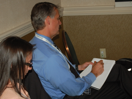 Attendees busily took notes during the presentations, including Daniela Gamble and Kevin Neal,...