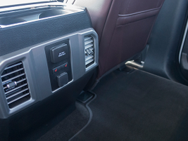The rear of the center console includes climate and seat heater controls, as well as two power...