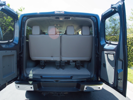 The van offers three rows of seating and a rear cargo space for luggage.