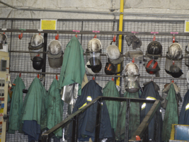 Workers who come in contact with super hot materials are equipped with protective head gear,...